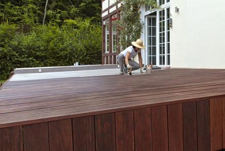 Frau streicht Terrasse mit Naturholzöl